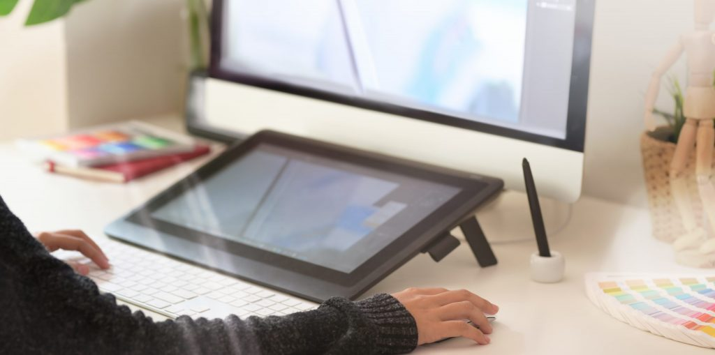 Graphic designer using digital drawing tablet and computer in studio